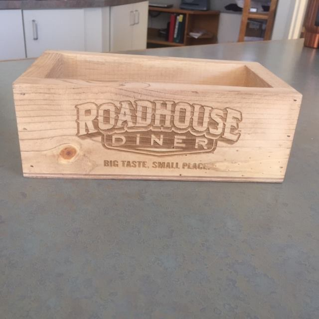 We can laser your logo onto a variety of items. Here's an example of a local business logo lasered onto wood.